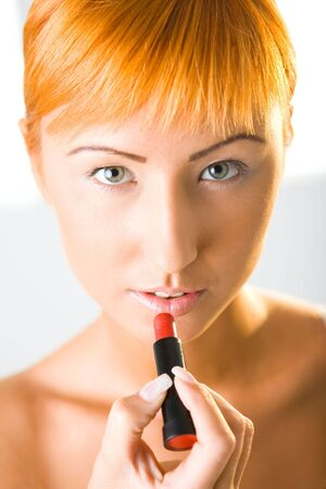 Beautiful woman applying red lipstick. Shes looking at camera. Closeup on face. Front view. photo