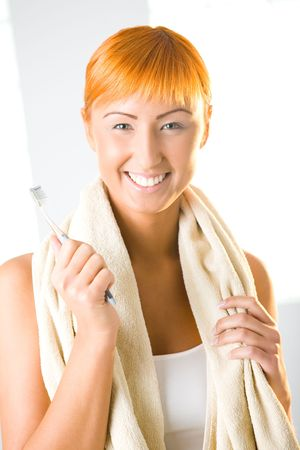 Young beauty woman with toothbrush and towel. Shes smiling and looking at camera. Front view. photo