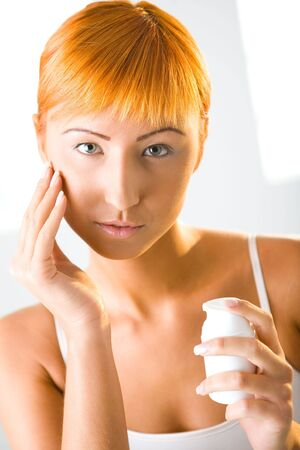 Beauty woman applying face cream. Shes looking at camera. Front view. photo
