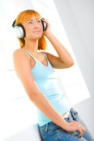 Young sexy woman listening to music by headphones. photo