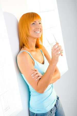 Young red-haired woman standing at wall with glass. Shes smiling and looking up. photo