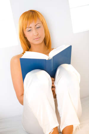 Young woman sitting on bed and reading book. Shes leaning against a wall. Front view. photo