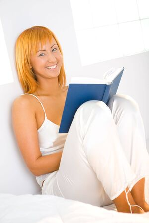 Young woman sitting on bed and holding book. Shes leaning against a wall. Shes smiling and looking at camera. photo