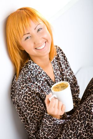 Young red-haired woman dressed pyjamas sitting on bed with cup of coffee. Shes leaning against a wall. Shes smiling and looking at camera. photo