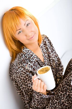 Young red-haired woman dressed pyjamas sitting on bed with cup of coffee. She's leaning against a wall. She's smiling and looking at camera. photo