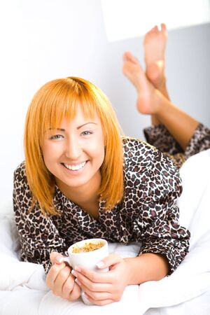 Young red-haired woman dressed pyjamas lying in bed with cup of coffee. Shes smiling and looking at camera. photo
