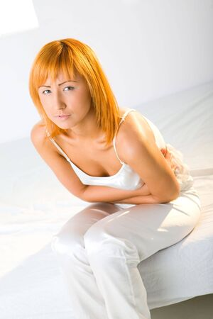 Young woman with stomachache sitting on bed. Shes hugging her abdomen. Looking at camera.