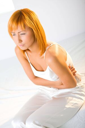 Young woman with stomachache sitting on bed. She's hugging her abdomen. photo