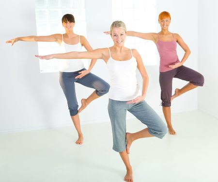 Group of women doing fitness exercise. Theyre looking at camera. Front view.