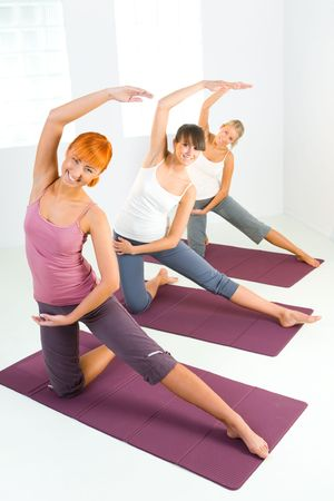 Group of women doing fitness exercise on mat. Theyre looking at camera.