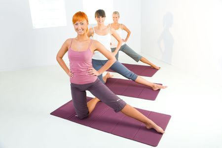 sportswoman: Group of women doing fitness exercise on mat. Theyre looking at camera.