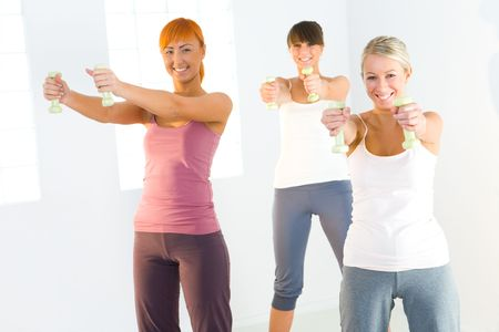 Group of women doing fitness exercise with dumbbells. Theyre looking at camera. photo