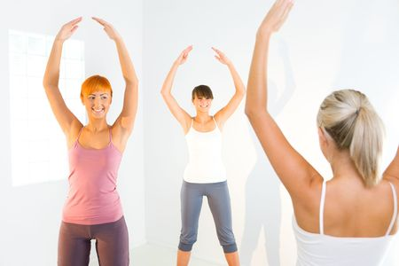 Three women standing with hands raised up and exercising.