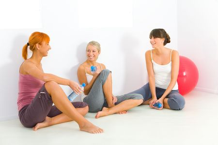 aerobic training: Group of women dressed sportswear sitting on the floor. They holding water bottles and talking. Stock Photo