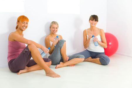 Group of women dressed sportswear sitting on the floor. They holding water bottles and looking at camera. photo
