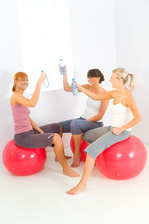 sportswoman: Group of women dressed sportswear sitting on big balls. They raise a toast with water bottles. Stock Photo