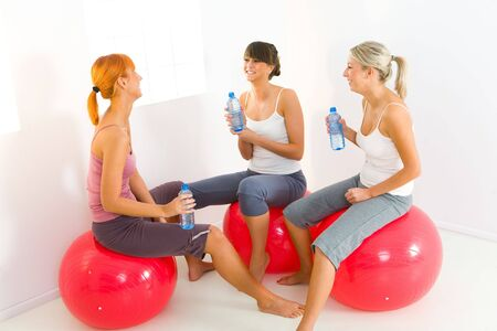 Group of women dressed sportswear sitting on big balls. They holding water bottles and talking. photo