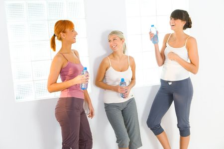 Group of women dressed sportswear standing at wall. They holding water bottles and talking.