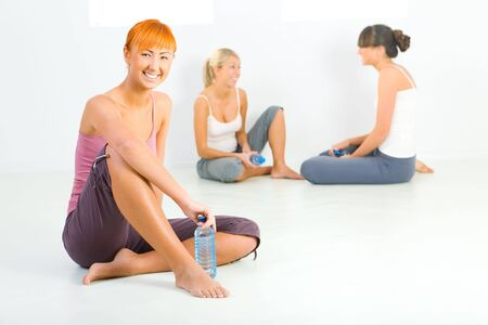 Group of women dressed sportswear sitting on the floor. They holding water bottles and talking. Closeup on red-haired woman. photo