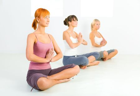 meditator: Three women sitting cross-legged on the floor and meditate.