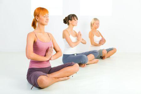 meditator: Three women sitting cross-legged on the floor and meditate. They have closed eyes.