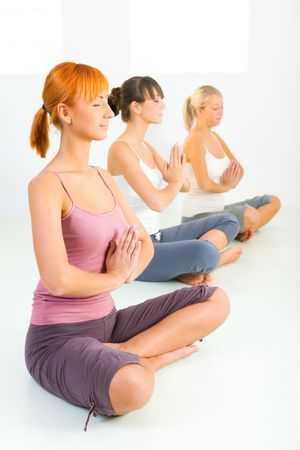 Three women sitting cross-legged on the floor and meditate. They have closed eyes.