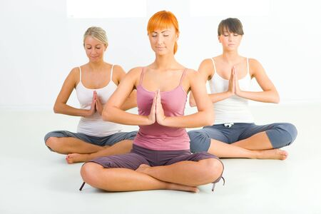 Three women sitting cross-legged on the floor and meditate. They have closed eyes. Front view.