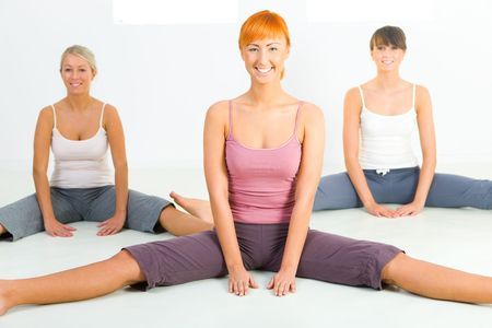 Group of women sitting on the floor and doing fitness exercise. They're looking at camera. Front view. Stock Photo - 3803624