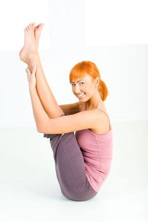 sportswoman: Young red-haired woman doing fitness exercise. Shes looking at camera. Side view. Stock Photo