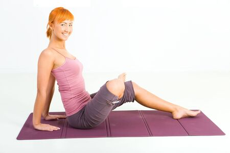 sportswoman: Young woman doing fitness exercise on mat. Shes looking at camera.