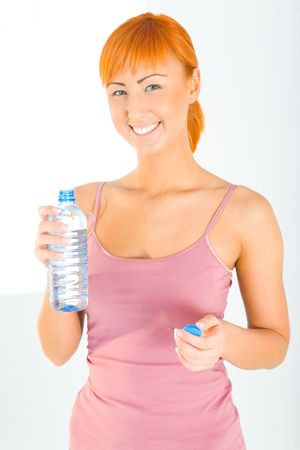 Young woman dressed sportswear holding water bottle. She's smiling and looking at camera. Front view. Stock Photo - 3803632