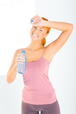 Young woman dressed sportswear holding water bottle. She's smiling and looking at camera. Front view. Stock Photo - 3803487