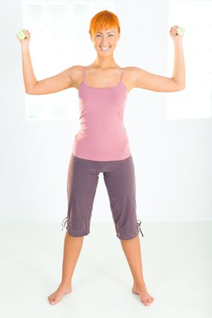 Young woman doing fitness exercise with dumbbells. Shes looking at camera. Front view. photo