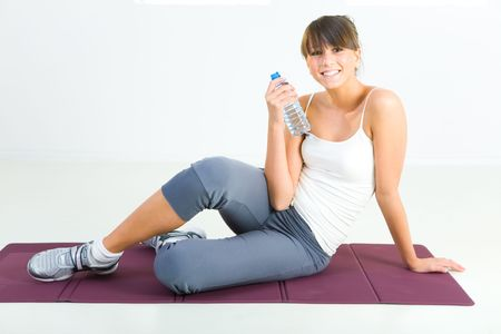 Young woman dressed sportswear sitting on mat and holding water bottle. She's smiling and looking at camera. Front view. Stock Photo - 3803597