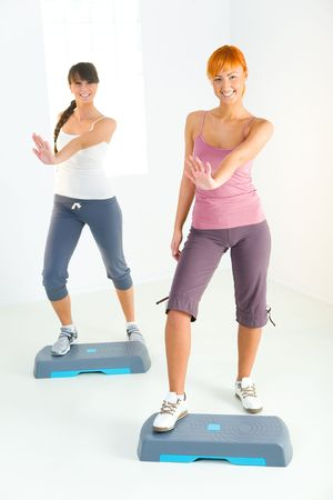 Two young women doing exercise on aerobic step. Theyre looking at camera. Front view. Stock Photo