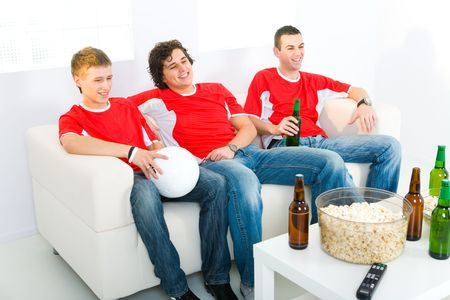 Three young men sitting on couch and watching soccer game on TV. photo