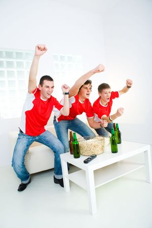 football party: Three happy sports fans get up from couch with raised hands. Stock Photo