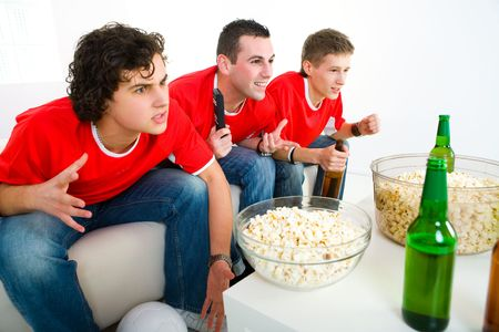 sport fan: Three exciting men sitting on couch and watching sport on TV.