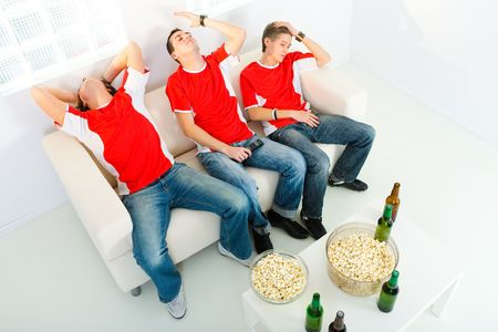 Three young men sitting on chouch and watching TV. They look disappointed. High angle view.