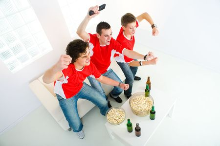 Three happy sports fans get up from couch with raised hands. High angle view. Stock Photo