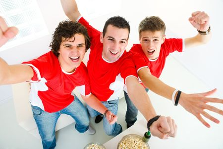 football party: Three happy sports fans get up from couch with raised hands. They looking at camera. High angle view. Stock Photo