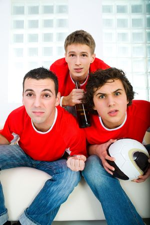 Three young men sitting on couch and watching soccer game on TV. Front view. Stock Photo - 3803691