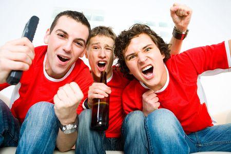 Tre uomini seduti su felice divano e guardare lo sport in TV.