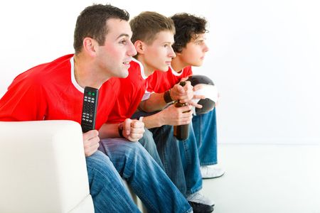 Three happy soccer fans sitting on couch and watching sport on TV. Side view. photo