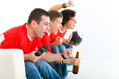football party: Three happy soccer fans sitting on couch and watching sport on TV. Side view.