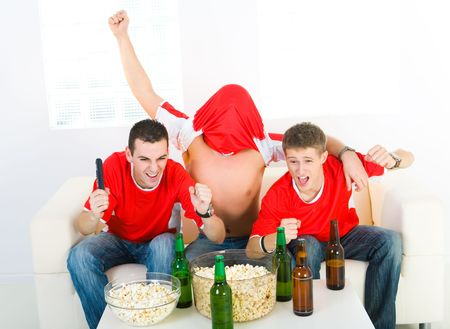 football party: Three exciting men sitting on couch and watching sport on TV. Front view.