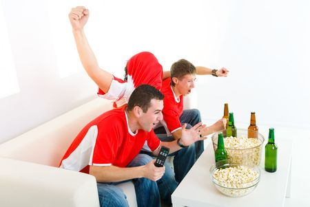 Three exciting men sitting on couch and watching sport on TV.