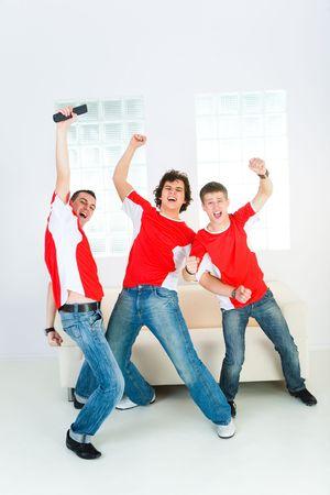 indoor soccer: Tres aficionados del deporte feliz levantarse de sof� con mano alzada. Vista frontal.
