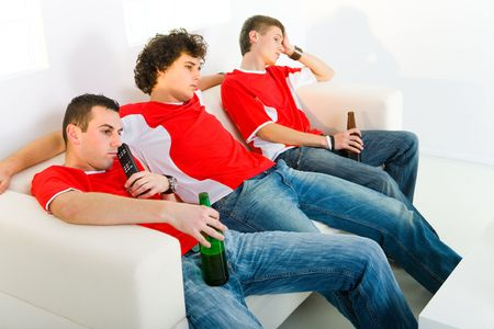 Three bored men sitting on couch and watching TV.