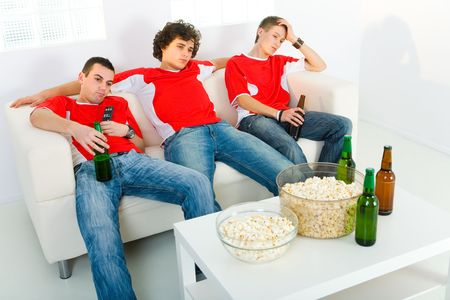 football party: Three bored men sitting on couch and watching TV.